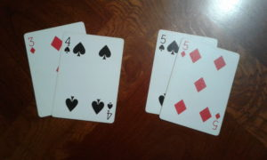 Right player leads third trick with two fives. Unable to beat both fives, the left player plays his two lowest cards.