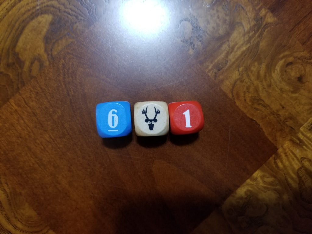 Deer in the Headlights contains three dice, one blue, one beige, and one red.
